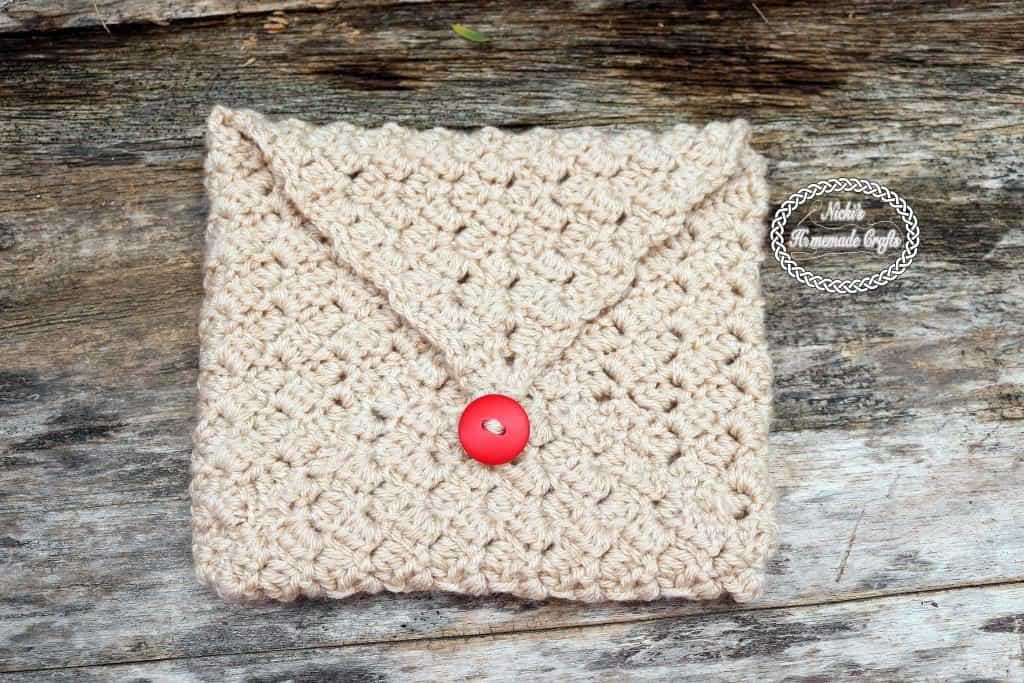 Crocheted corner to corner beige envelope with button on a wooden surface