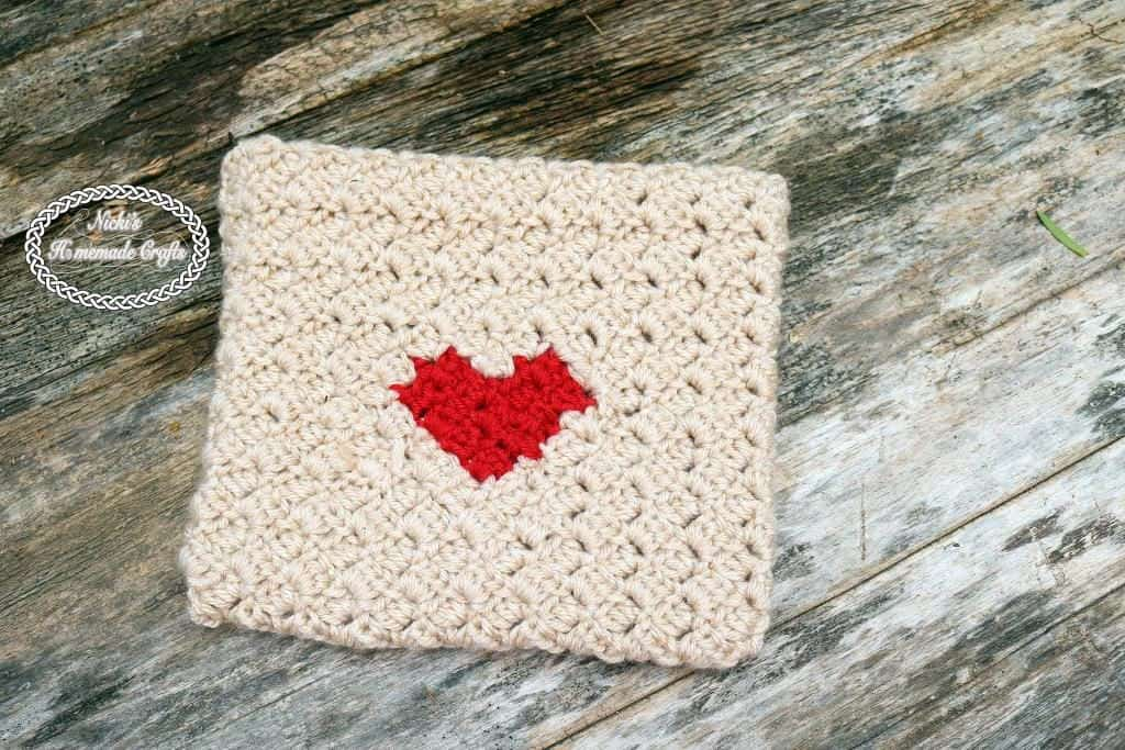 Crocheted beige envelope with heart on a wooden surface