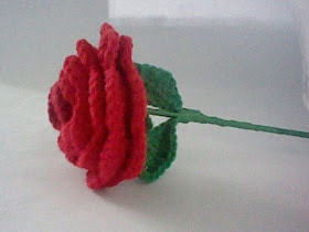 Crocheted red rose with green leaves on a white surface