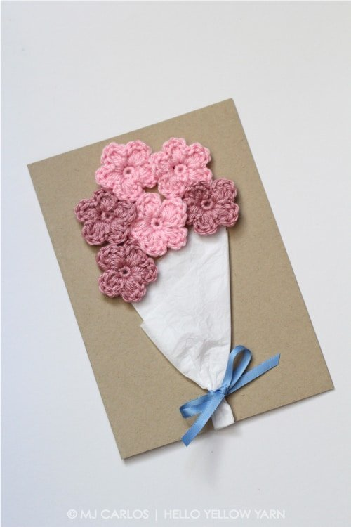 Crocheted pink flowers as a bouquet on a brown envelope on a white surface