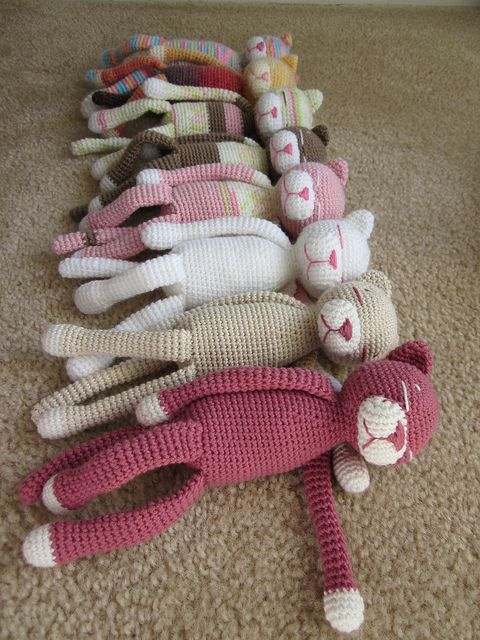 8 crochet animals sleeping colorful cat amigurumis on a brown carpet