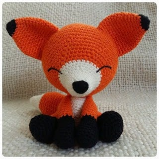 Crocheted Sleeping orange fox sitting on a messy surface