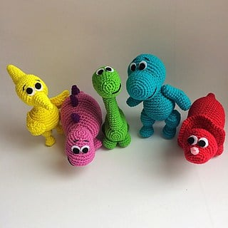 Crochet animals: Yellow, pink, green, blue and red dinosaur on a white background and surface