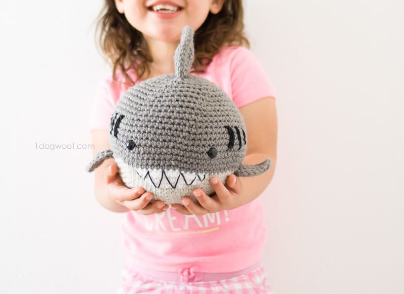 Crocheted grey white shark with teeth being held by a laughing girl with pink shirt in front of a white surface