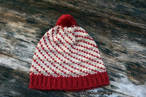 The Swirly Heart Hat Crochet Pattern features red and white colors shown as hearts swirling around the hat to the red ribbing or the red pom-pom. This pattern features the waistcoat stitch aka knit stitch.