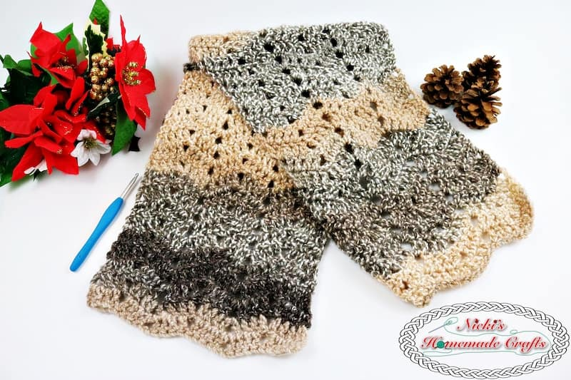 Hazel Chevron Scarf which is a Free Crochet Pattern and uses the Peephole Chevron Stitch which is displayed with christmas flowers and a pinecone by Nicki's Homemade Crafts #chevron #hazel #barcelona #yarn #stitch #peephole #tutorial #video #free #crochet #pattern