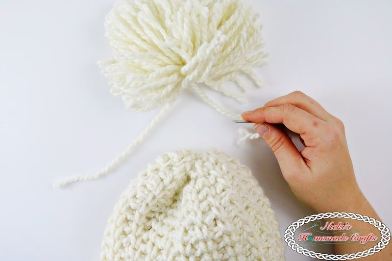 Attach the Pom pom to Chunky Knit-Like Hat which is a Free Crochet Pattern by Nicki's Homemade Crafts