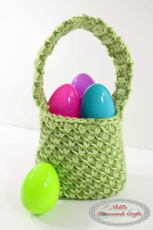 Mini Crochet Easter Egg Basket featuring the Turkish Star Stitch displayed with pink, purple, blue and green plastic ester eggs on a white surface and background.