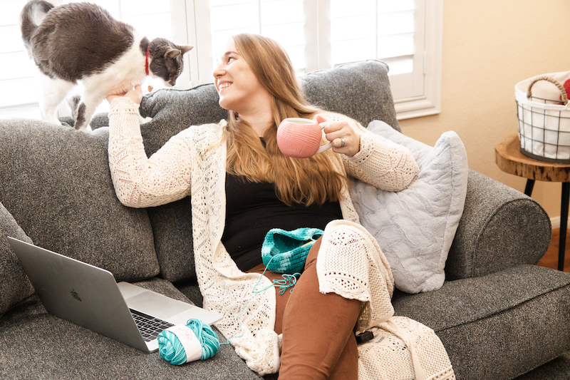 Gato se aconchega enquanto faz crochê